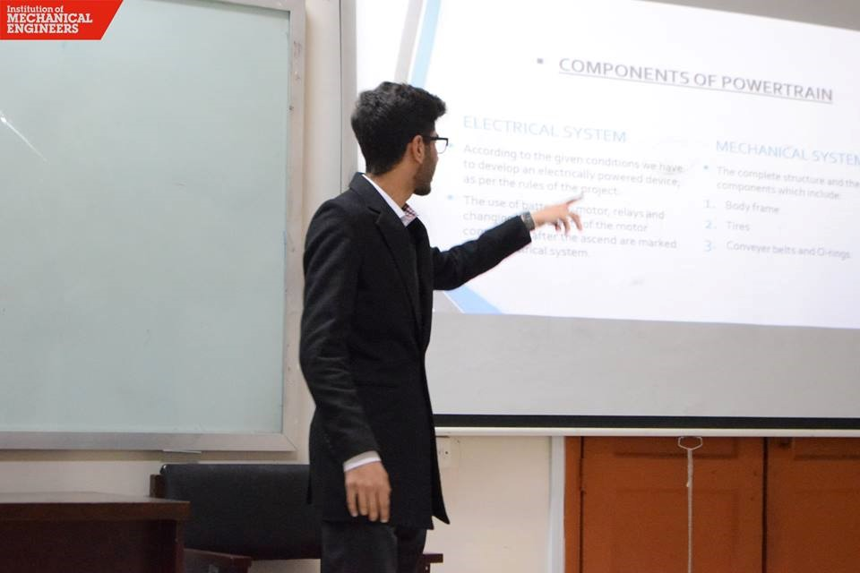 A student explaining his team's choice of systems during the presentations